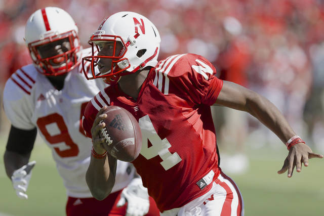 Red team quarterback Tommy Armstrong Jr. (4) runs past White team's Avery Moss during the annual Nebraska Red-White NCAA college football spring game in Lincoln, Neb., Saturday, April 6, 2013. (AP Photo/Nati Harnik)