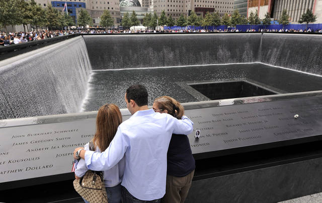 Family members of those who died in the Sept. 11, 2001 World Trade Center attacks, gather at the edge of the north reflecting pool of the Sept. 11 memorial during 10th anniversary ceremonies at the site, in New York, Sunday Sept. 11, 2011. (AP Photo/Justin Lane, Pool)