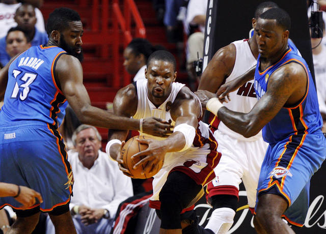 Miami's Chris Bosh (1) works between Oklahoma City's James Harden (13) and  Kendrick Perkins (5) during Game 3 of the NBA Finals between the Oklahoma City Thunder and the Miami Heat at American Airlines Arena, Sunday, June 17, 2012. Photo by Bryan Terry, The Oklahoman