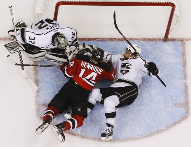 Los Angeles Kings goalie Jonathan Quick (32) and teammate Jarret Stoll (28) defend the goal against New Jersey Devils' Adam Henrique (14) during the third period of Game 5 of the NHL hockey Stanley Cup finals Saturday, June 9, 2012, in Newark N.J.(AP Photo/Julio Cortez)