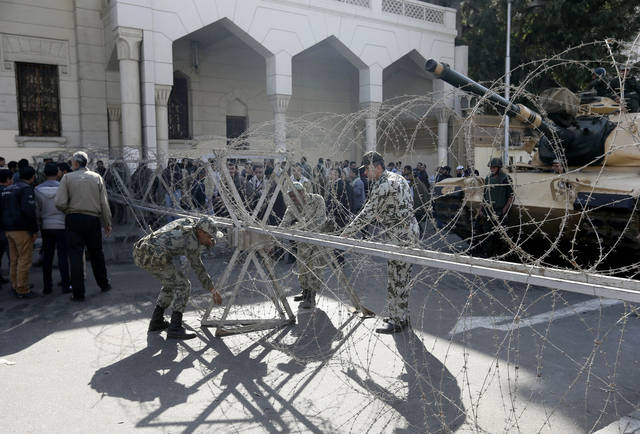 Egyptian Army deploy near the presidential palace to secure  the site of overnight clashes between supporters and opponents of President Mohammed Morsi in Cairo, Egypt, Thursday, Dec. 6, 2012. The Egyptian army has deployed tanks outside the presidential palace in Cairo following clashes between supporters and opponents of Mohammed Morsi that left several people dead and hundreds wounded. (AP Photo/Hassan Ammar)