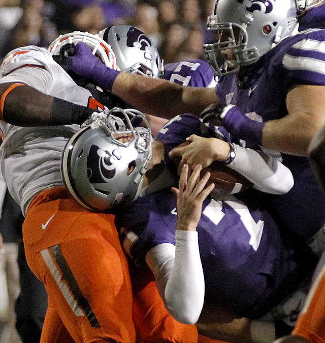 Oklahoma State's Calvin Barnett (99) gets the face mask of Kansas State's Collin Klein (7) during the college football game between the Oklahoma State University Cowboys (OSU) and the Kansas State University Wildcats (KSU) at Bill Snyder Family Football Stadium on Saturday, Nov. 1, 2012, in Manhattan, Kan. Photo by Chris Landsberger, The Oklahoman