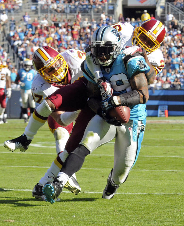Carolina Panthers' Steve Smith, front, catches a pass as Washington Redskins' Reed Doughty (37) and Josh Wilson (26) defend during the fourth quarter of an NFL football game in Charlotte, N.C., Sunday, Oct. 23, 2011. The Panthers defeated the Redskins 33-20. (AP Photo/Mike McCarn)
