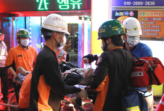 Rescue workers carry an injured person on a stretcher from a karaoke bar, where a fire broke out, in Busan, South Korea, Saturday, May 5, 2012. Nine people were reportedly killed in the blaze. (AP Photo/Yonhap) KOREA OUT