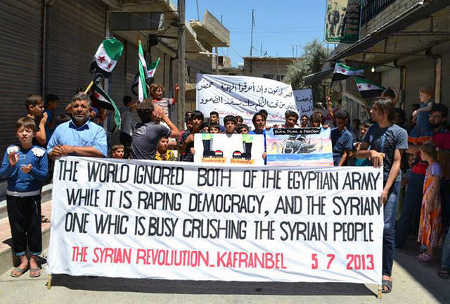 This citizen journalism image provided by Edlib News Network, ENN, which has been authenticated based on its contents and other AP reporting, shows anti-Syrian regime protesters holding banners and Syrian revolution flags during a demonstration at Kafr Nabil town in Idlib province, northern Syria, Friday, July 5, 2013. Syria's main opposition bloc on Friday urged the international community to take action to protect civilians in the cities of Homs and Daraa that have been targeted by military as part of a government campaign to regain control of the territory it lost to the opposition. (AP Photo/Edlib News Network ENN)