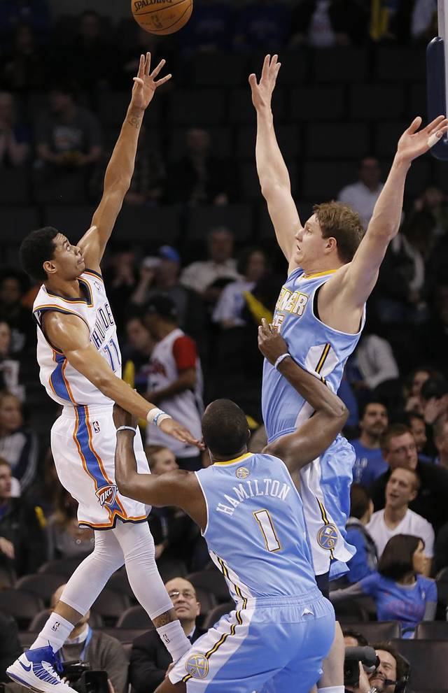 Oklahoma City's Jeremy Lamb (11) shoots over Denver's Timofey Mozgov (25) and Jordan Hamilton (1) during the NBA basketball game between the Oklahoma City Thunder and the Denver Nuggets at the Chesapeake Energy Arena on Wednesday, Jan. 16, 2013, in Oklahoma City, Okla.  Photo by Chris Landsberger, The Oklahoman