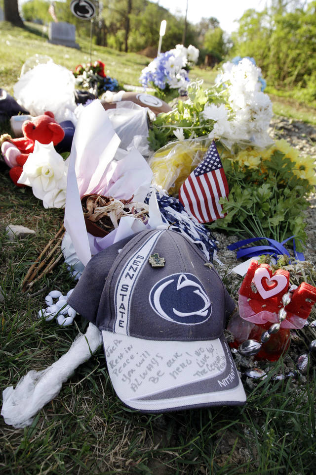 In this Friday, April 20, 2012, photo, Penn State hats, flowers and footballs decorate the gravesite of former Penn State football coach Joe Paterno in State College, Pa. No apparent images of the late Paterno were shown on the Beaver Stadium video screens for Saturday's Blue-White game. But the Hall of Fame coach remains an endearing figure to Penn State fans, from the blue and white carnations left at the Paterno statue outside the stadium to a 5K race run Sunday in his name. (AP Photo/Keith Srakocic)