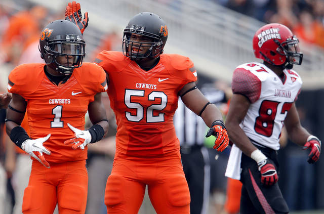 CELEBRATION: Oklahoma State's Kevin Peterson (1) and Ryan Simmons (52) celebrate a defensive play in front of Louisiana-Lafayette's Darryl Surgent (87) during a college football game between Oklahoma State University (OSU) and the University of Louisiana-Lafayette (ULL) at Boone Pickens Stadium in Stillwater, Okla., Saturday, Sept. 15, 2012. Photo by Sarah Phipps, The Oklahoman