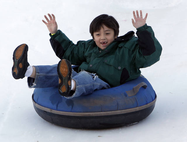 Aiden Gillespie, 7, tubes down a snow slope at Chickasaw Bricktown Ballpark in Oklahoma City, Saturday, Nov. 24, 2012.  Photo by Garett Fisbeck, The Oklahoman