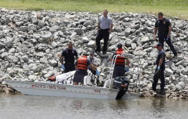 Oklahoma City Police and Fire Dept. personnel cover a body found partially submerged on the bank of the Oklahoma River under the Exchange Ave. bridge in Oklahoma City, OK, Monday, May 28, 2012. Photo by Paul Hellstern