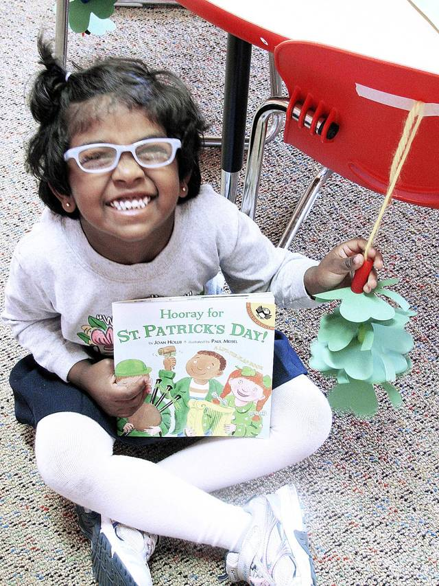 Aashna Paul holds the class St. Paddy's book and shows off her leprechaun ladder last week during St. Patrick's Day festivities at St. John Nepomuk Catholic School in Yukon. Their teacher makes the ladders with the students every year, and they tape them to the backs of their chairs in hopes the leprechaun will pay them a visit. In the morning, the students arrive to find glitter dust that he has left behind and some chocolate gold coins as a treat.  Photo provided by St. John Nepomuk Catholic School