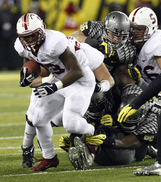 Stanford running back Stepfan Taylor, left, breaks away from Oregon defenders during the first half of their NCAA college football game in Eugene, Ore., Saturday, Nov. 17, 2012. (AP Photo/Don Ryan)