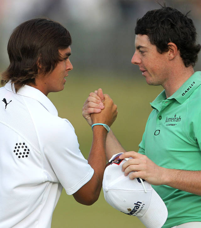 Northern Ireland's Rory McIlroy, right, and Rickie Fowler of the U.S. shake hands at the end of their round on the 18th green during the second day of the British Open Golf Championship at Royal St George's golf course Sandwich, England, Friday, July 15, 2011. (AP Photo/Tim Hales)