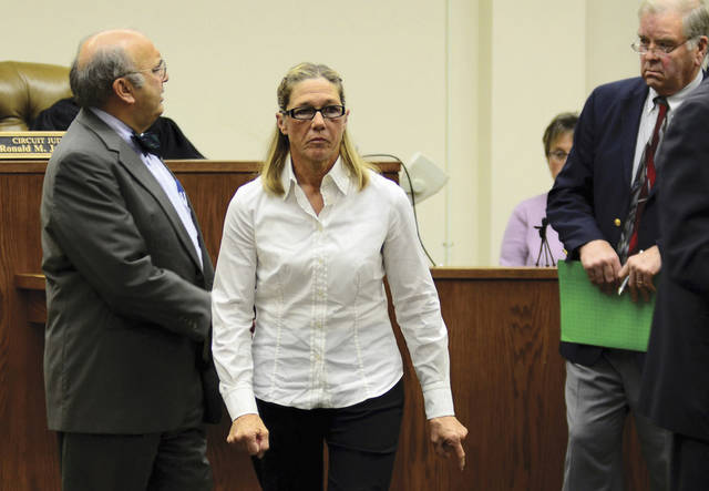 FILE - In this Oct. 22, 2012 file photo, former Dixon, Ill., comptroller Rita Crundwell leaves a courtroom in Dixon with her attorney Paul Gaziano, left, after making her first appearance in the northern Illinois city to face charges she siphoned millions of dollars in public funds into a secret bank account. On Wednesday, Nov. 14, 2012, Crundwell is expected to plead guilty at federal court in Rockford, Ill., to stealing $53 million to fund a lavish lifestyle while overseeing the public finances of the city of Dixon. (AP Photo/Sauk Valley Media, Alex T. Paschal, File)