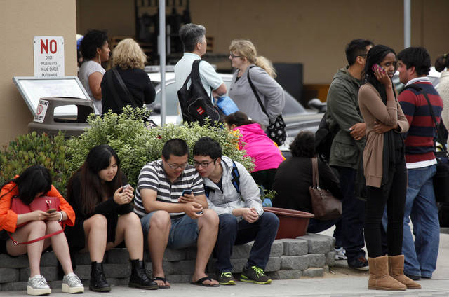 Santa Monica College students wait for police clearance to pick up their vehicles after a shooting on campus Friday June 7, 2013 in Santa Monica. A gunman with an assault-style rifle killed at least six people in Santa Monica on Friday before police shot him to death in a gunfight in the Santa Monica College library. (AP Photo/Nick Ut)