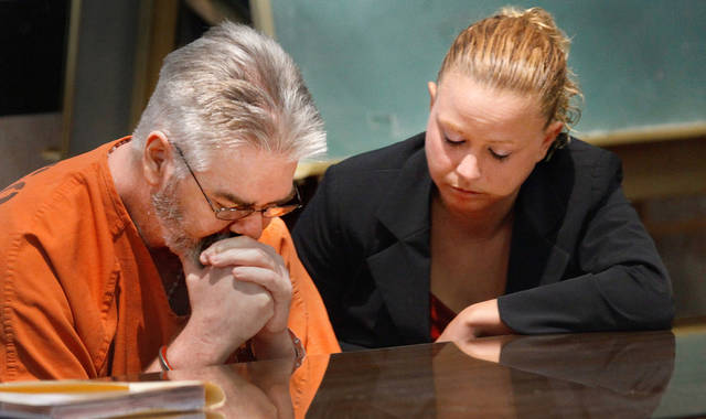 Kyle Eckardt sits at the defense table, hands in cuffs and head lowered. At right is Emily Kirkpatrick, one of his defense attorneys.