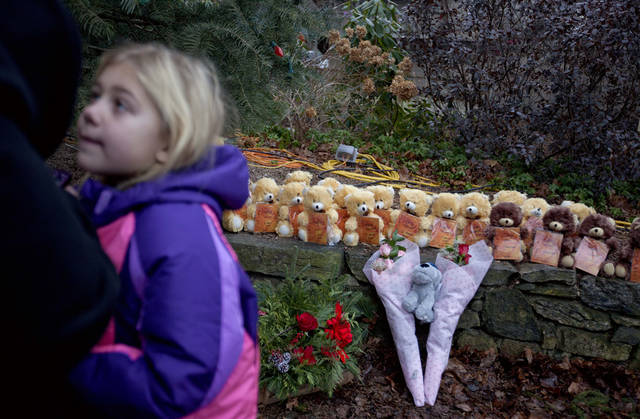 Ava Staiti, 7, of New Milford, Conn., looks up at her mother Emily Staiti, while visiting a sidewalk memorial with 26 teddy bears, each representing a victim of the Sandy Hook Elementary School shooting, Sunday, Dec. 16, 2012, in Newtown, Conn. A gunman walked into Sandy Hook Elementary School in Newtown Friday and opened fire, killing 26 people, including 20 children. (AP Photo/David Goldman) ORG XMIT: CTDG118
