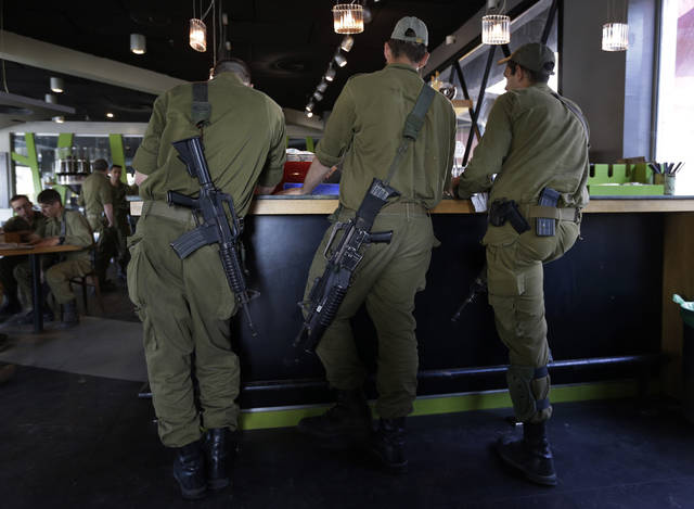 Israeli soldiers wait for their drinks at a coffee shop at Yad Mordechai, in southern Israeli close to the Israel Gaza Strip Border, Tuesday, Nov. 20, 2012. On Tuesday, grieving Gazans were burying militants and civilians killed in ongoing Israeli airstrikes, and barrages of rockets from Gaza sent terrified Israelis scurrying to take cover. Efforts to end a week-old convulsion of Israeli-Palestinian violence drew in the world's top diplomats Tuesday, with U.S. President Barack Obama dispatching his secretary of state to the region on an emergency mission and the U.N. chief appealing from Cairo for an immediate cease-fire. (AP Photo/Lefteris Pitarakis)