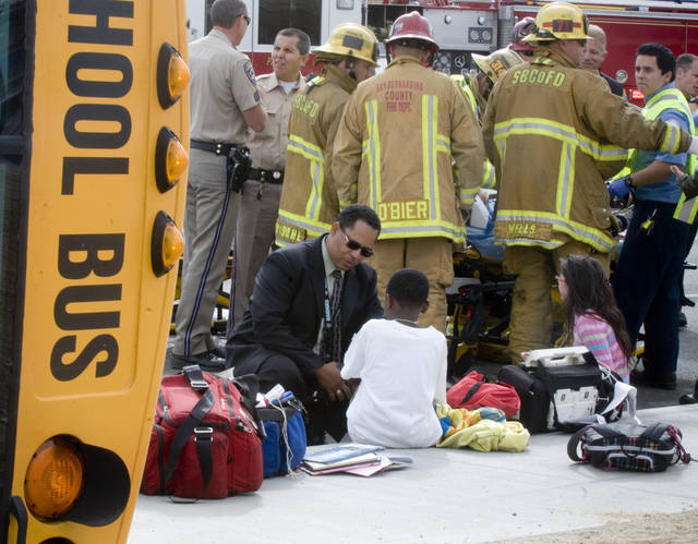 Victorville School officials talk to some students while others are treated after a school was struck and overturned on Nisqualli Road in Victorville Calif. Thursday October 11, 2012. A school bus carrying 40 children in Southern California has been knocked on its side in a crash that has injured 13 children and the bus driver. (AP Photo/The Victor Valley Daily Press, James Quigg)
