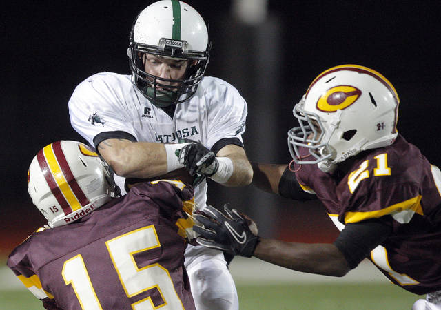 Catoosa Cole Scheulen is tackled by Clinton's Jake Reynolds (15) and Jalee Rainge tackle during the high school playoff game between Clinton and Catoosa at Putnam City High School.,  Friday, Nov. 25, 2011.  Photo by Sarah Phipps, The Oklahoman