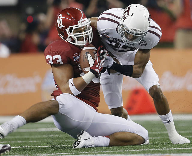 Texas A&M's Dustin Harris (22) puts a hit on Oklahoma's Trey Millard (33) as he catches the ball during the college football Cotton Bowl game between the University of Oklahoma Sooners (OU) and Texas A&M University Aggies (TXAM) at Cowboy's Stadium on Friday Jan. 4, 2013, in Arlington, Tx. Photo by Chris Landsberger, The Oklahoman