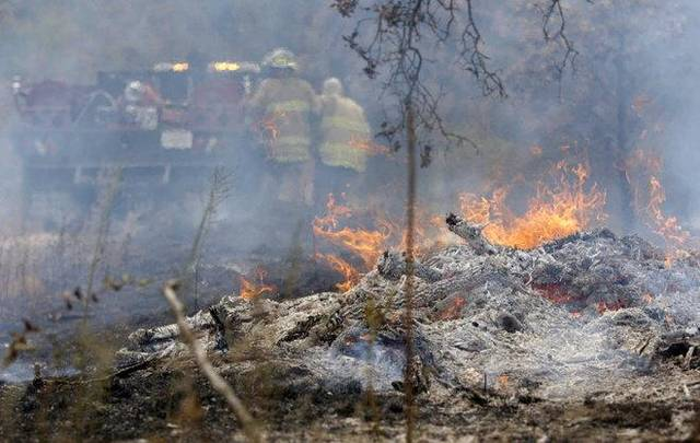 In this Aug. 5 file photo, Mannford firefighters work to battle a wildfire just west of Mannford on West 31st Street MIKE SIMONS/Tulsa World File