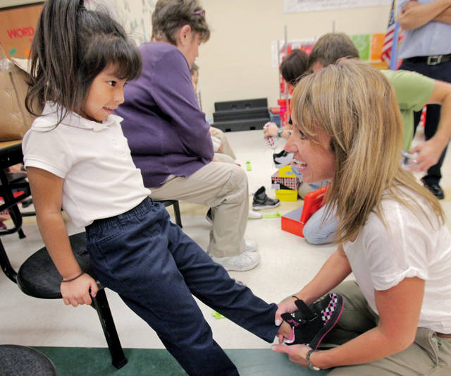 Kindergartner Joselin Orozcon gets some help from Laura Ketcherside trying on shoes.  Metro Shoe Warehouse is giving away shoes to students at Stand Watie Elementary, Wednesday, September 26, 2012. Photo By David McDaniel/The Oklahoman