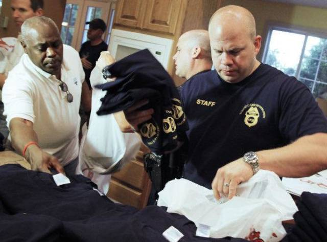 "From left, Oklahoma City police captain Nate Tarver, Edmond Police patrol officer Jeff Morefield and Oklahoma City police sergeant Bryan Husted organize t-shirts for a fundraiser for injured Oklahoma City police officer Chad Peery, at the City Bites Corporate Headquarters, 2600 E Memorial, in Edmond, Okla., Friday, June 10, 2011. The ""Taking Care of Our Own"" fundraiser for injured Oklahoma City police officer Chad Peery is scheduled for 1 to 9 p.m. at AMF Boulevard Lanes in Edmond. Photo by Nate Billings, The Oklahoman ORG XMIT: KOD"