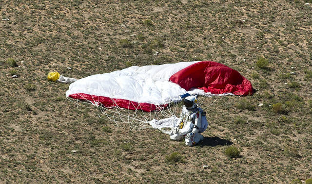 In this photo provided by Red Bull, pilot Felix Baumgartner of Austria lands in the desert after his successful jump on Sunday, Oct. 14, 2012 in Roswell, N.M. Baumgartner came down safely in the eastern New Mexico desert minutes about nine minutes after jumping from his capsule 128,097 feet, or roughly 24 miles, above Earth (AP Photo/Red Bull, Predrag Vuckovic)  ORG XMIT: NY209