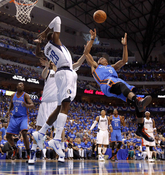 Oklahoma City's Russell Westbrook (0) is fould as he shoots in front of Dallas' Ian Mahinmi (28) and Dirk Nowitzki during Game 4 of the first round in the NBA playoffs between the Oklahoma City Thunder and the Dallas Mavericks at American Airlines Center in Dallas, Saturday, May 5, 2012. Photo by Bryan Terry, The Oklahoman