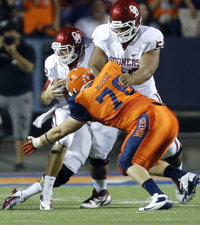 Oklahoma Sooners quarterback Landry Jones (12) is sacked by UTEP's Ruben Munoz (76) during the college football game between the University of Oklahoma Sooners (OU) and the University of Texas El Paso Miners (UTEP) at Sun Bowl Stadium on Saturday, Sept. 1, 2012, in El Paso, Tex.  Photo by Chris Landsberger, The Oklahoman