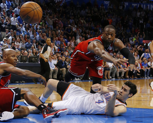 Oklahoma City's Nick Collison (4) passes the ball under Miami's Dwyane Wade (3) as Ray Allen (34) watches during an NBA basketball game between the Oklahoma City Thunder and the Miami Heat at Chesapeake Energy Arena in Oklahoma City, Thursday, Feb. 15, 2013. Miami won 110-100. Photo by Bryan Terry, The Oklahoman