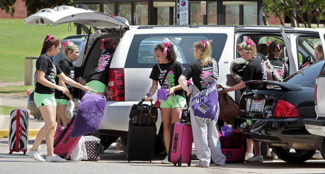Students from Vian unload their luggage Tuesday as they get ready for a cheer camp at the University of Oklahoma. Middle and high school students from across the state participated in a cheer camp this week at the University of Oklahoma. OU offers a variety of sports camps throughout the summer season.  PHOTO BY STEVE SISNEY, THE OKLAHOMAN