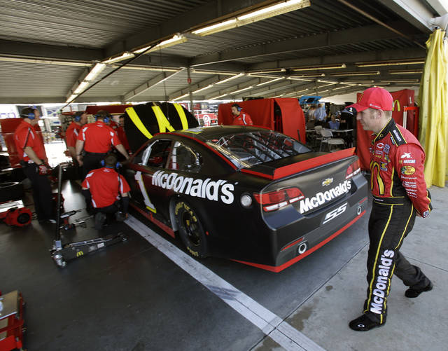 Jamie McMurray, right, watches as crew members make adjustments to his car in his garage during NASCAR auto race testing at Daytona International Speedway, Friday, Jan. 11, 2013, in Daytona Beach, Fla. (AP Photo/John Raoux)