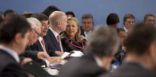 U.S. Secretary of State Hillary Clinton, center right, speaks with British Foreign Minister William Hague, center left, during a meeting of NATO foreign ministers at NATO headquarters in Brussels on Tuesday, Dec. 4, 2012. NATO foreign ministers are expected to approve Turkey's request for Patriot anti-missile systems to bolster its defense against possible strikes from neighboring Syria. (AP Photo/Virginia Mayo)