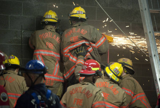 Firefighters work to free a woman who fell part of the way down the 20-foot wall and got stuck between two buildings in Portland, Ore., Wednesday, Jan. 16, 2013.  Firefighters cut a hole through concrete and used an air bag and a soapy lubricant to free the woman.  The woman spent about four hours in a space 8 to 10 inches wide before rescuers managed to free her as television cameras filmed much of the effort.  Firefighters said they hadn't gotten a clear explanation of the woman's predicament. Lt. Rich Chatman of the Portland fire department,  said she had been seen smoking or walking on the roof of a two-story building before she fell. (AP Photo/The Oregonian, Brent Wojahn)  MAGS OUT; TV OUT; LOCAL TV OUT; LOCAL INTERNET OUT; THE MERCURY OUT; WILLAMETTE WEEK OUT; PAMPLIN MEDIA GROUP OUT