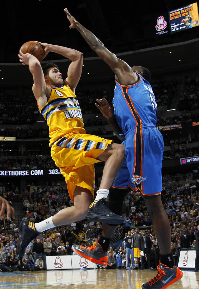 Denver Nuggets forward Danilo Gallinari, left, of Italy, shoots as Oklahoma City Thunder forward Kendrick Perkins defends in the fourth quarter of their NBA basketball game in Denver, Sunday, Jan. 20, 2013. The Nuggets won 121-118 in overtime. (AP Photo/David Zalubowski)