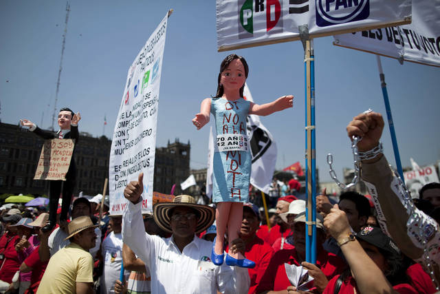 FILE - In this May 1, 2012, file photo, a demonstrator holds up a statue depicting Mexican actress Angelica Rivera, center, wife's of Enrique Pena Nieto, then presidential candidate for the Institutional Revolutionary Party (PRI), during a Labor Day march in Mexico City. Most Mexicans agree the country's dysfunctional labor laws need to be retooled. What they don't agree on is how, with a new proposal to loosen work rules and increase union democracy threatening to create the first big political battle for President-elect Enrique Pena Nieto. At left, another demonstrator holds a statue depicting Pena Nieto. (AP Photo/Dieu Nalio Chery, file)
