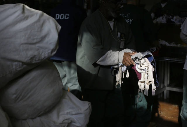 An inmate carries bras that were laundered at Central Maryland Correctional Facility in Sykesville, Md., Thursday, Dec.  13, 2012, as part of a breast cancer awareness campaign. Nearly 10,000 bras were expected to be laundered by the inmates after they were collected by a radio station in Frederick, Md. One dollar for each bra was donated to breast cancer research, and the cleaned bras are expected to be donated to women's shelters. Inmates at the facility annually handle more than 2.2 million pounds of laundry from state agencies and non-profit organizations in Maryland. (AP Photo/Patrick Semansky)