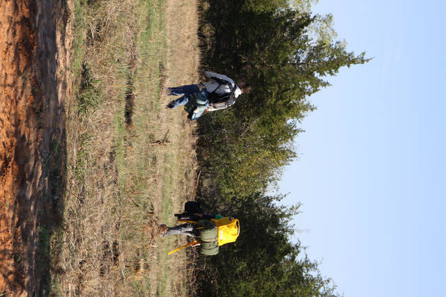 Dusty Buff, left, and Philip Nguyen trek across a field to find a campsite for the night. The two pastors with Grace Church in Norman spent 10 days living as homeless people. PHOTO PROVIDED BY DUSTY BUFF <strong></strong>