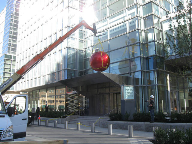 A crane installs the first Christmas bulb near the west entrance at Devon Energy Center along Hudson Avenue. Photo by Steve Lackmeyer, The Oklahoman <strong></strong>