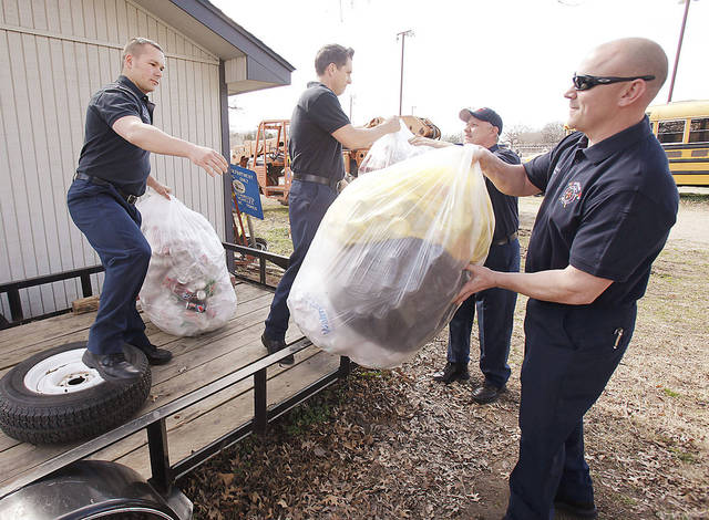 Bethany firefighter Chris Allbritton (left), Driver Billy Greenwood, Captain Jason Mahaffey, and firefighter John Card load cans onto a flatbed trailer in Bethany to benefit the firefighters association. The association uses the money collected from this program to help child burn victims. PHOTOS BY PAUL HELLSTERN, THE OKLAHOMAN