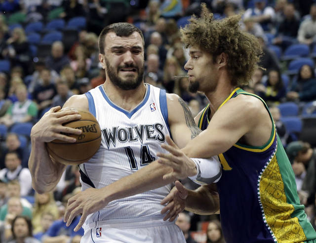 Minnesota Timberwolves' Nikola Pekovic of Montenegro, left, protects the ball from New Orleans Hornets defender Robin Lopez in the first quarter of an NBA basketball game Saturday, Feb. 2, 2013 in Minneapolis. (AP Photo/Jim Mone)