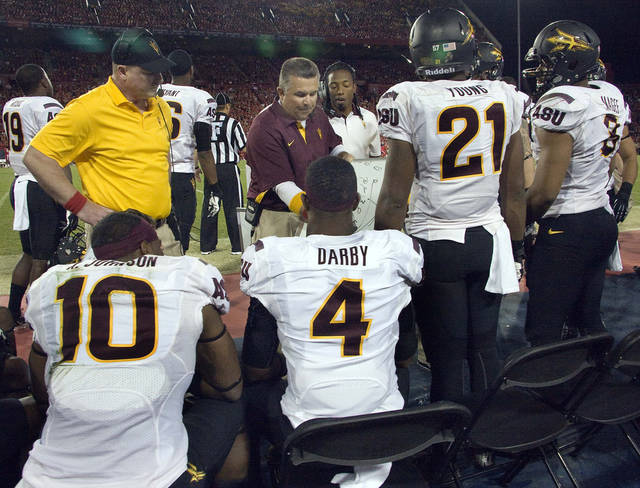 Arizona State coach Todd Graham, center, diagrams a play for players Keelan Johnson (10), Alden Darby (4), Chris Young (21), and Brandon Magee (8) during the first half of an NCAA college football game against Arizona at Arizona Stadium in Tucson, Ariz., Friday, Nov. 23, 2012. (AP Photo/Wily Low)