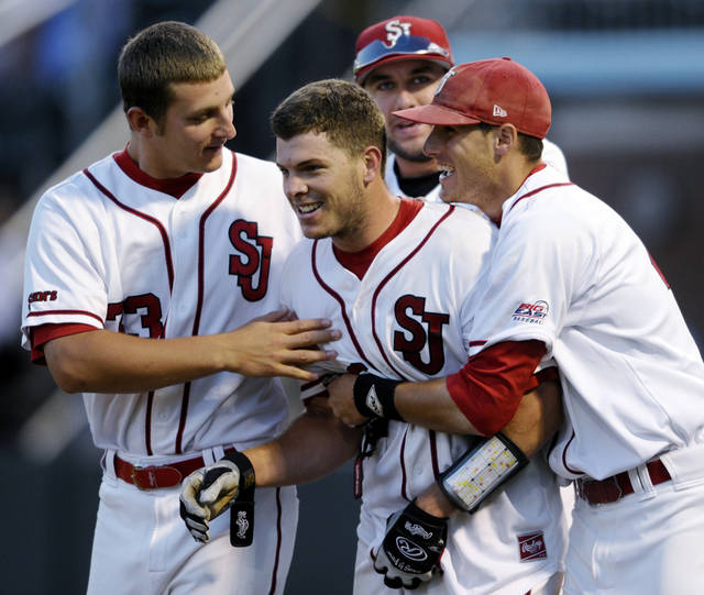 St. John's Danny Bethea (26) is congratulated by teammates Eric Peterson, left, and Pat Talbut, right, after his home run in the ninth inning against North Carolina during an NCAA college baseball tournament regional game, Saturday, June 2, 2012, in Chapel Hill, N.C. St. John's won 5-4. (AP Photo/Sara D. Davis)