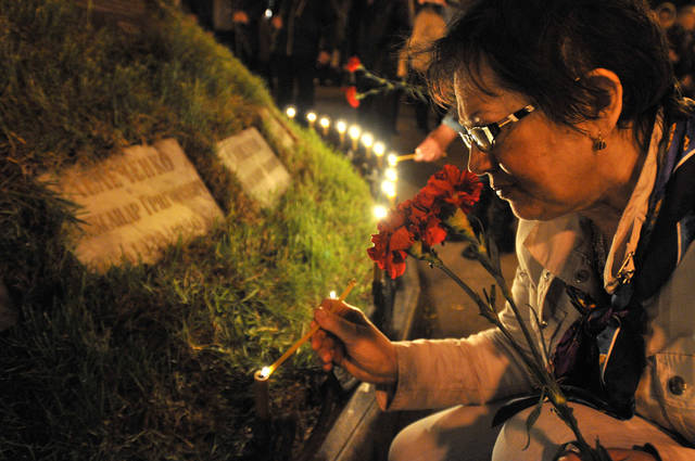 Woman lights candles to honor the memory of the victims of the Chernobyl disaster in Kiev, Ukraine,Thursday, April 26, 2012. Ukrainian President Viktor Yanukovych on Thursday paid tribute to the victims of the Chernobyl nuclear disaster and said his country is committed to building a new, safer shelter over the reactor as Ukrainians, Belarusians and Russians marked the 26th anniversary of the world's worst nuclear disaster. (AP Photo/Sergei Chuzavkov)