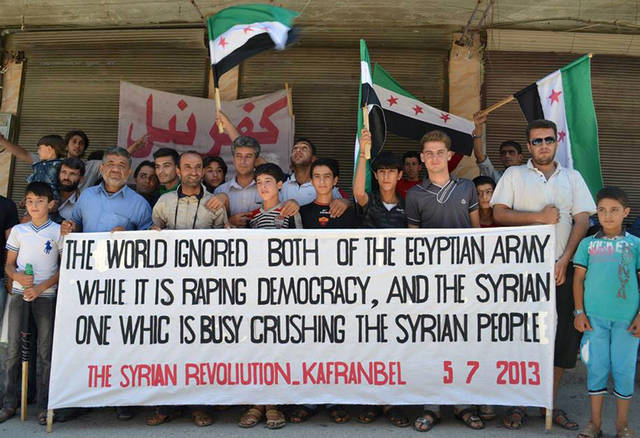This citizen journalism image provided by Edlib News Network, ENN, which has been authenticated based on its contents and other AP reporting, shows anti-Syrian regime protesters holding a banner and Syrian revolution flags during a demonstration at Kafr Nabil town in Idlib province, northern Syria, Friday, July 5, 2013. Syria's main opposition bloc on Friday urged the international community to take action to protect civilians in the cities of Homs and Daraa that have been targeted by military as part of a government campaign to regain control of the territory it lost to the opposition. (AP Photo/Edlib News Network ENN)