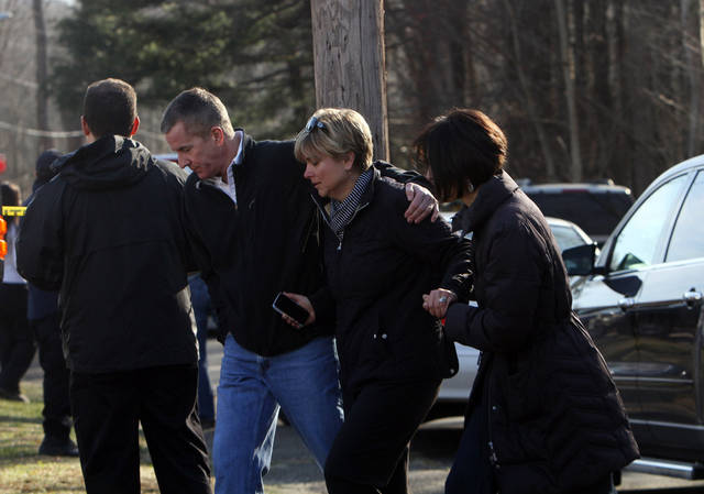 Teachers walk away from the Sandy Hook Elementary School in Newtown, Conn. following a shooting where authorities say a gunman opened fire, leaving 27 people dead, including 20 children, Friday, Dec. 14, 2012. (AP Photo/The Journal News, Frank Becerra Jr.) MANDATORY CREDIT, NYC OUT, NO SALES, TV OUT, NEWSDAY OUT; MAGS OUT ORG XMIT: NYWHI108