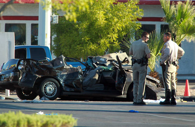 Police officers stands near a vehicle involved in a crash at a bus stop, Thursday, Sept. 13, 2012 in Las Vegas. Police suspect a driver was drunk and speeding Thursday morning when his vehicle went airborne, spun out and plowed into a Las Vegas bus stop, killing four pedestrians and injuring eight others. Las Vegas police officer Laura Meltzer said four people were in the vehicle and had to be extricated following the crash a little before 6:30 a.m. on Spring Mountain Road east of Decatur Boulevard. (AP Photo/Las Vegas Review-Journal, Jeff Scheid) LOCAL TV OUT; LOCAL INTERNET OUT; LAS VEGAS SUN OUT