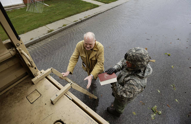 "Maryland National Guard Sgt. Zachary Greene holds a bible for Harold ""Doc"" Sterling as he prepares to climb the ladder into a National Guard truck to be evacuated from his home after the effects of superstorm Sandy Tuesday, Oct. 30, 2012, in Crisfield, Md. (AP Photo/Alex Brandon) ORG XMIT: MDAB109"